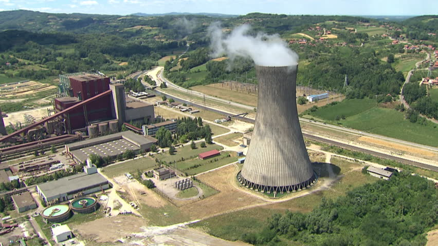 Aerial shot of a Power Plant and its cooling tower with steam rising from it and