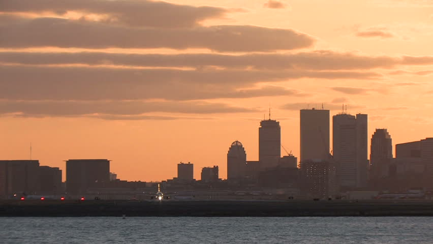 Airplane takeoff from Logan Airport, Boston at sunset