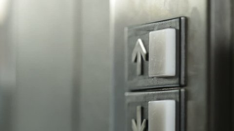 Manicured finger presses the button for an elevator but it doesn't light up, so they press it again and again. Dolly shot.