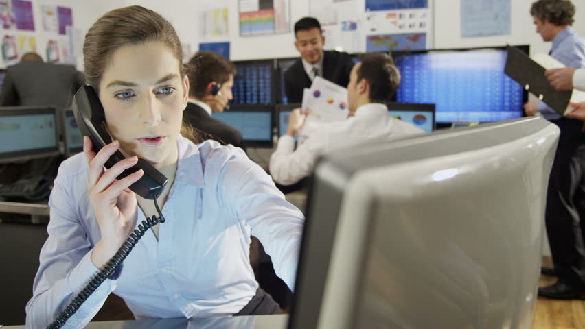 Beautiful female city worker takes a phone call at her desk in a busy office filled with computers. Her colleagues are hard at work in the background.