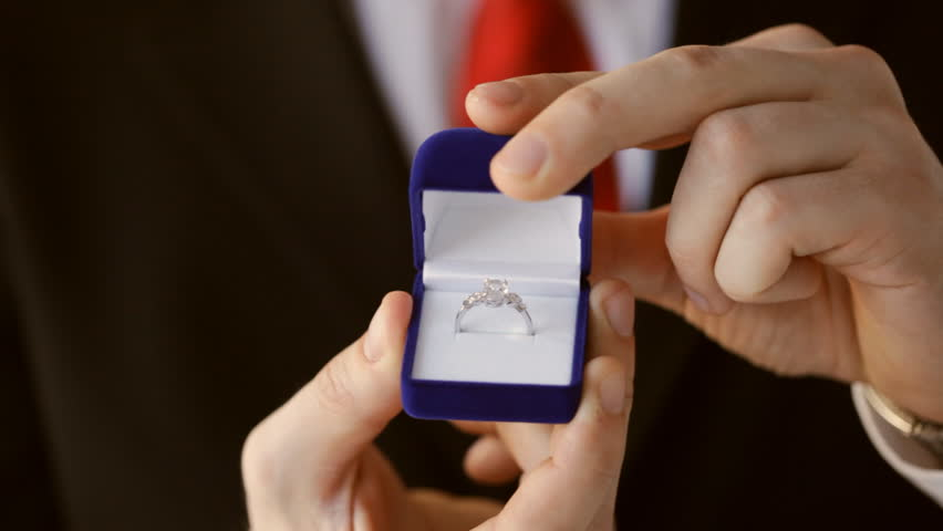 groom or salesman holding a box with wedding ring