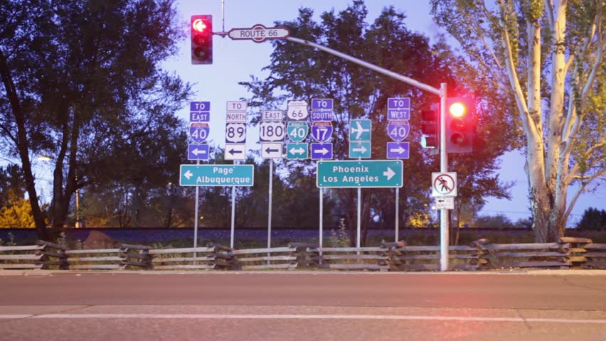 Time-lapse of Historic Route 66 at dawn with traffic streaking in front of flashing signals and signs. | Shutterstock HD Video #3675359
