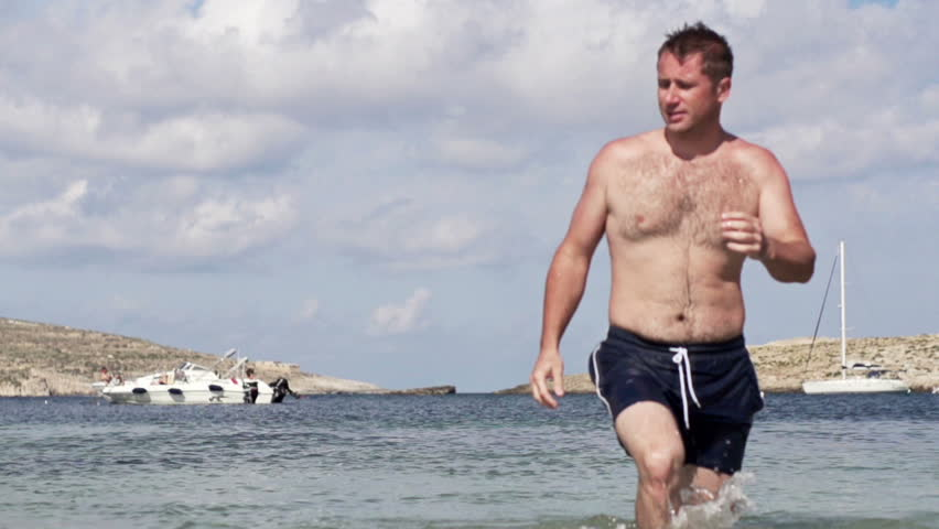 Stock Video of Slow motion: Young half naked man walk