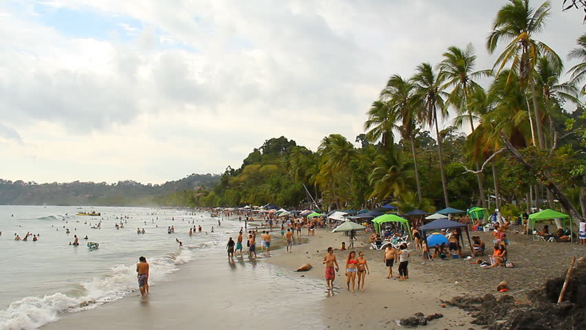 "COSTA RICA - MAR 2013: Mostly local ""Ticos"" gathered on a beach just outside Manuel Antonio National Park in Quepos, Costa Rica in March, 2013."