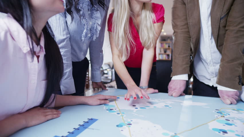 A multi-ethnic business team are working in a light and modern open plan office. They are looking at a map of the world and discussing possibilities for future business ventures. | Shutterstock HD Video #3702719