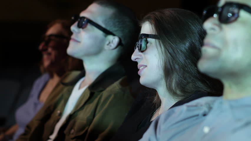 Young woman applauds as she watches a 3D movie. Focus on her with a small dolly move and projections on her face.