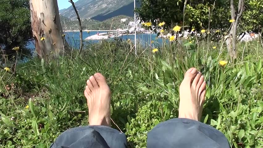 Resting on grass with shoes off, sea view