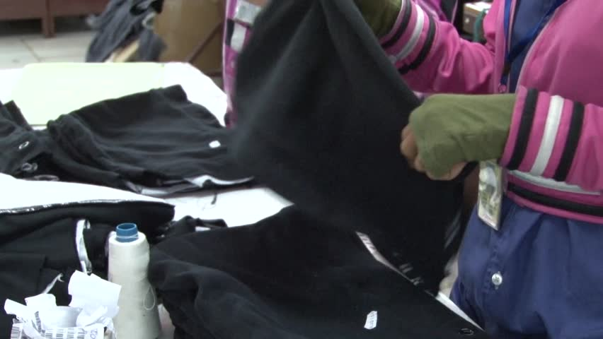 Medium close up two female workers'hands and arms sorting completed garments at their station in the factory