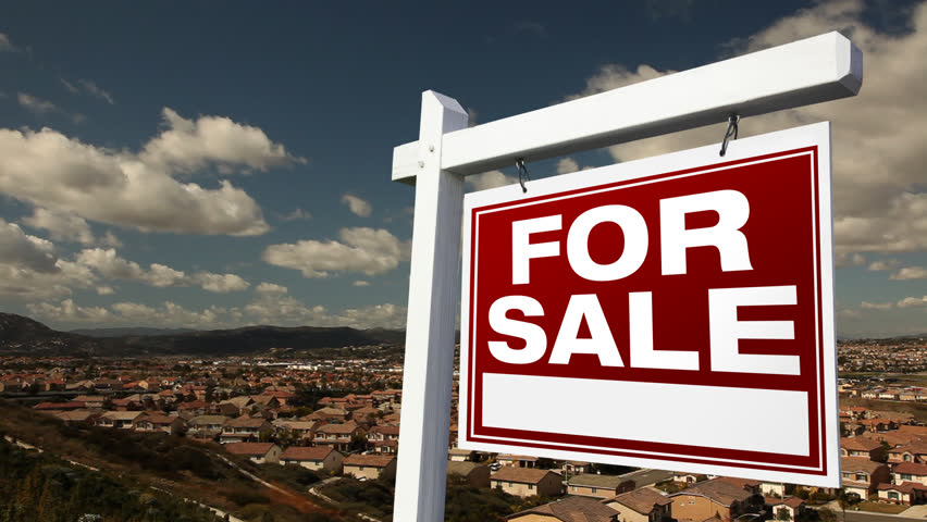 For Sale Real Estate Sign with Time-lapse Clouds and Neighborhood Below.
