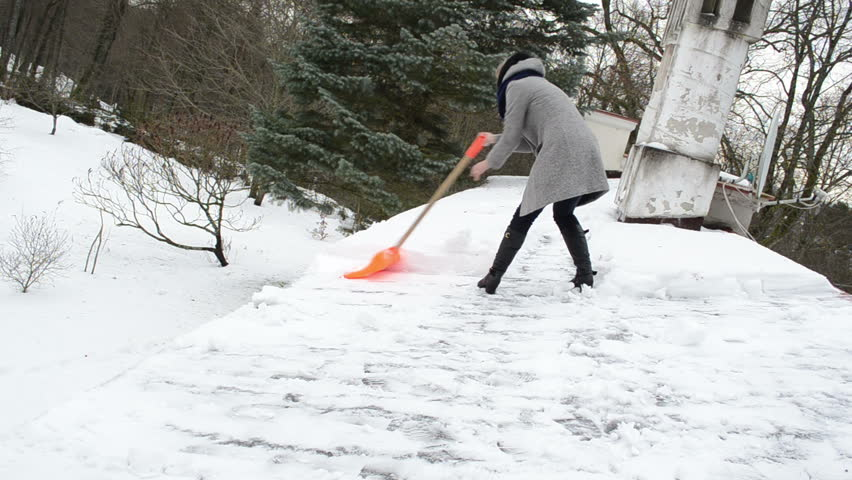 Lonely Poor Woman On Heel And Grey Coat Clean Snow With Orange Shovel From  House Roof