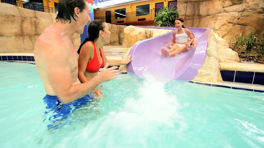 Part underwater Caucasian parents in swimming pool while children enjoy water slides at theme park