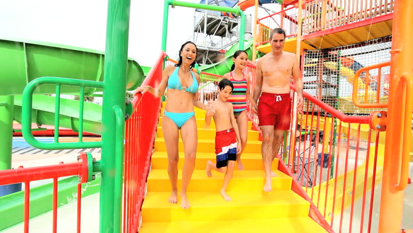 Young Caucasian family in swimwear enjoying outing at colorful water park