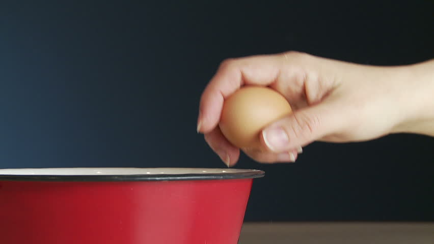 Hand cracks a fresh egg on the side of a red metal bowl and drops it into the