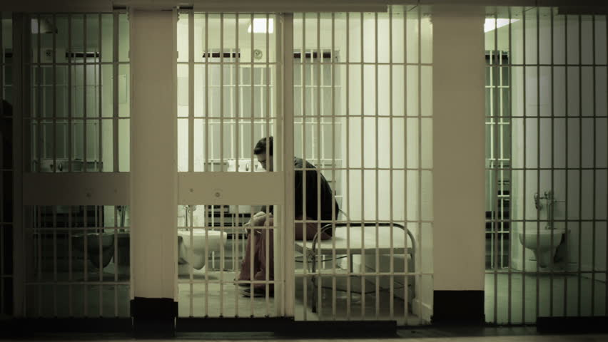 Inmate gets up from cot and stands at the bars in a prison cell. Desaturated color.