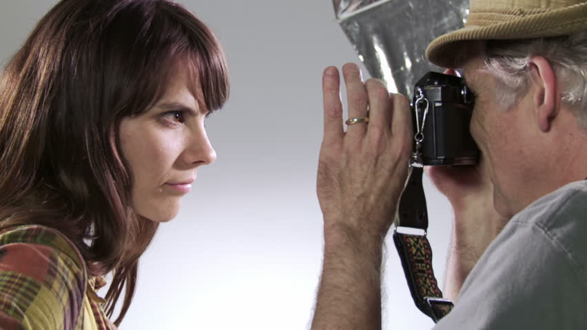 Photographer takes pictures of intense model Deliberately edgy, hand-held camera with manual zooms in studio.