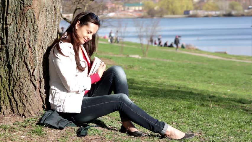 Happy female student doing homework in city park.Happy female student reading book in city park.  | Shutterstock HD Video #3761099