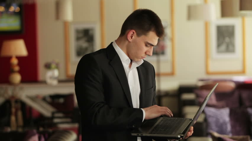 Businessman standing in a cafe with a laptop