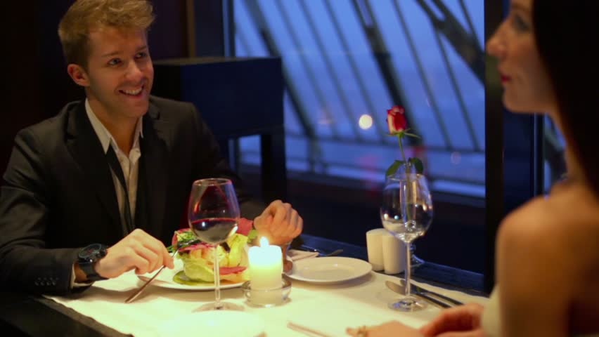 Waiter brings meal for brunette girl which sits at table with young guy