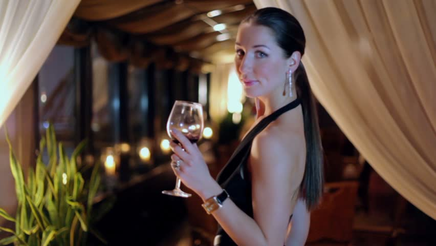 Young woman in black dress turns around, drinks wine from glass and then she walks away at dark restaurant