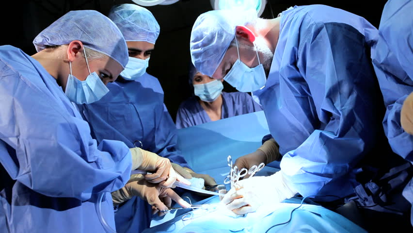 Doctors surgeons operate patient in operating theater