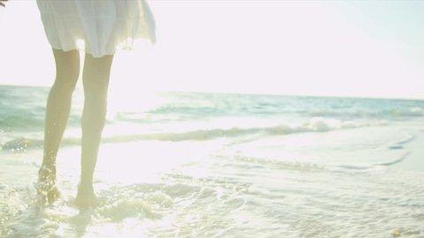 Legs feet Hispanic girl walking barefoot wet sand island beach sun lens flare shot on RED EPIC