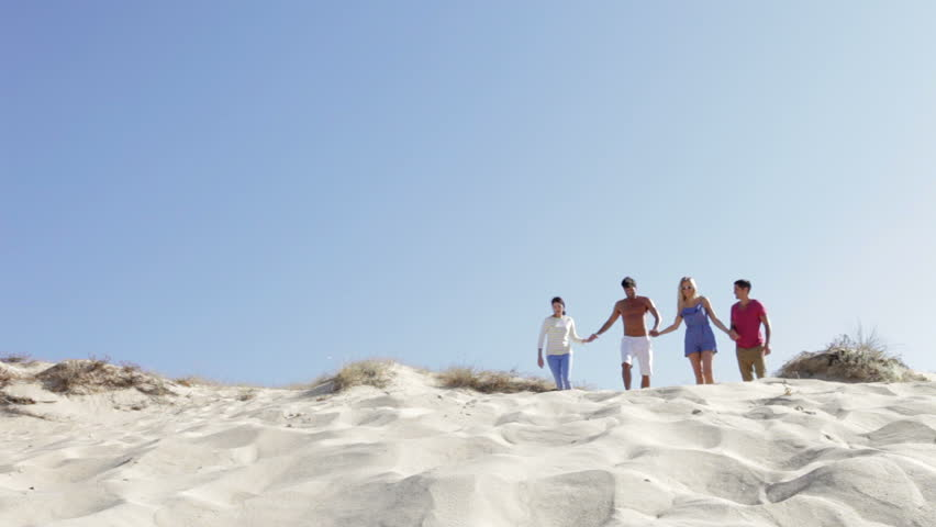 Group of friends in casual clothing running down sand dune towards camera position. Shot on Canon 5d Mk2 with a frame rate of 30fps