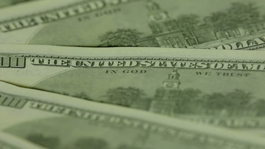"""Several hundred-dollar bills spinning. A narrow strip of focus - only """"IN GOD WE TRUST"""". Close-up 