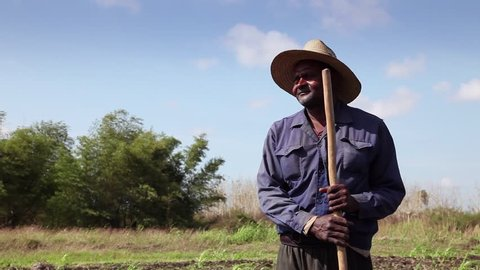GUINES, CUBA - CIRCA APRIL 2013: Beginning of the growing season, portrait of african american peasant with hat in Cuban farm field, circa April 2013 in Guines, Cuba