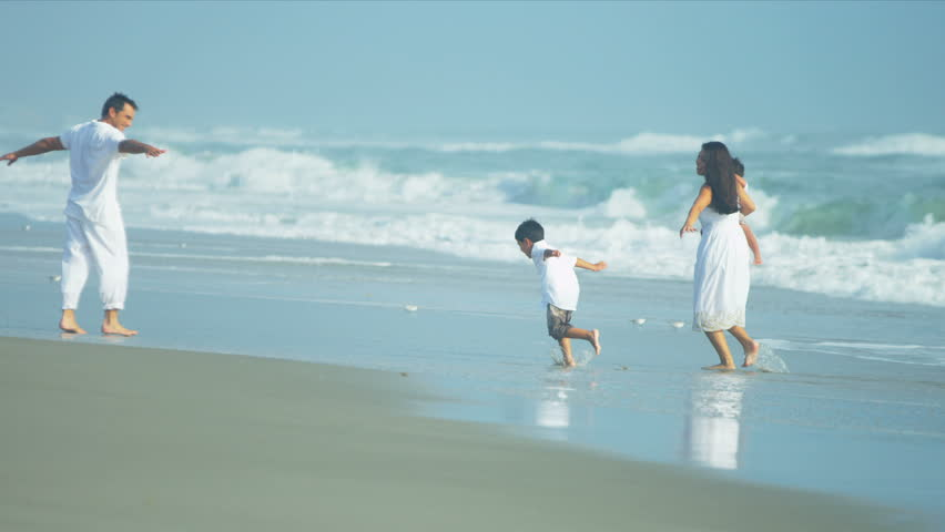 Hispanic young loving family spending vacation on beach playing in the ocean surf shot on RED EPIC