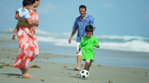 Latin American father enjoying kicking ball with young little kid on beach shot on RED EPIC