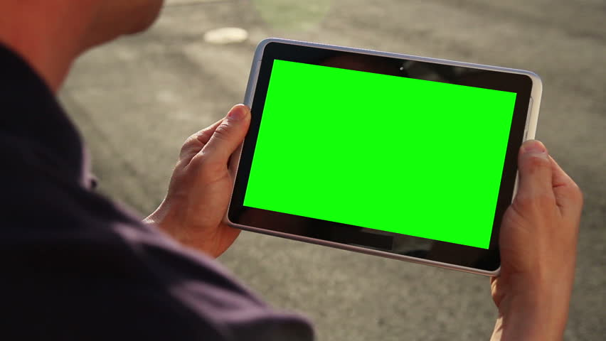 a man holds a blank tablet pc with a green screen for your own custom content