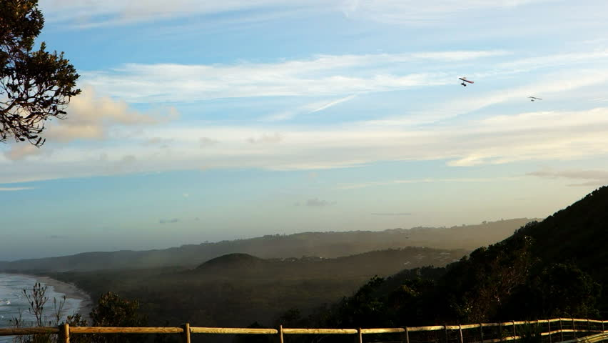 a long shot of two hang gliders flying above  tallows beach at cape byron, australia