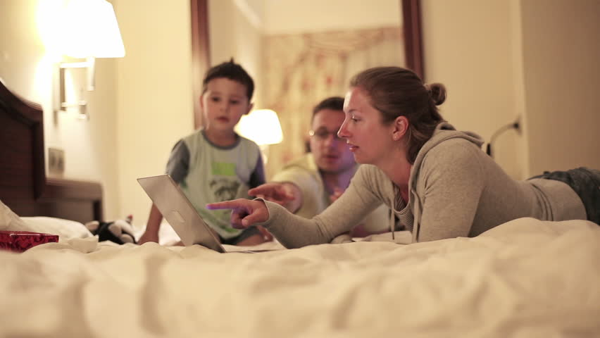 Happy family with laptop lying on bed, steadicam shot
