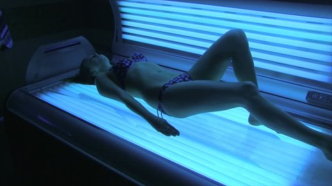 young girl lying in the tanning bed and sunbathing