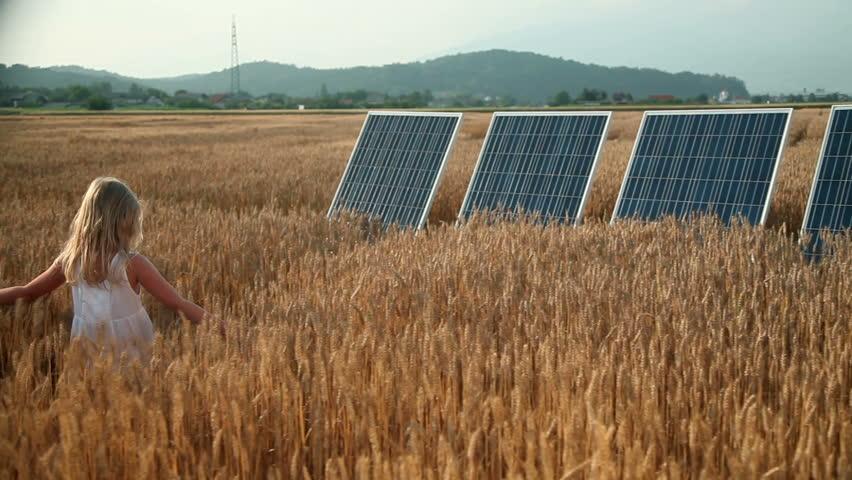 Little girl on a grain field with a solar power panels