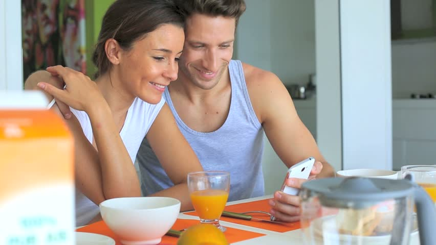 Couple looking at internet while having breakfast