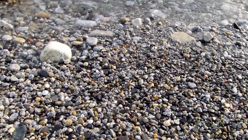 light blue water from the Mediterranean sea, with pebbles and rocks, from a beautiful beach in the island of Elba in Tuscany, Italy