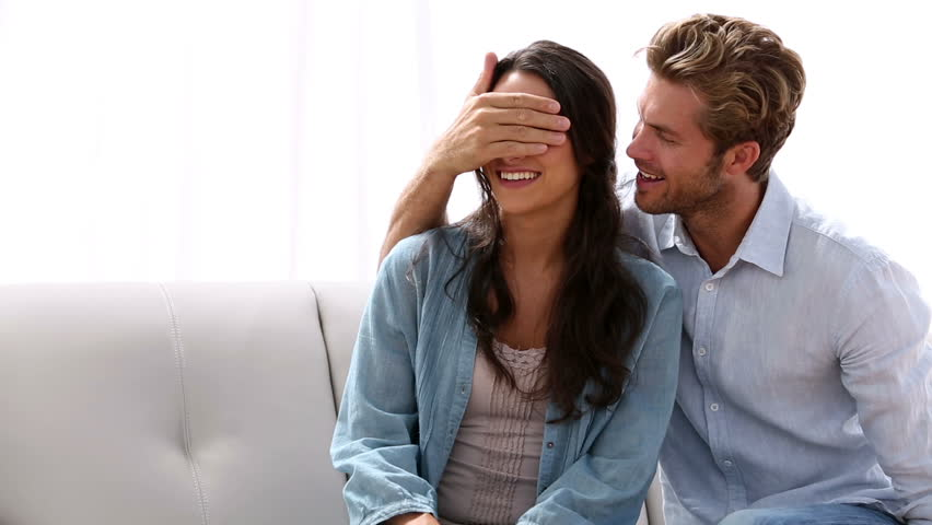 Man surprising his partner with engagement ring at home on the couch