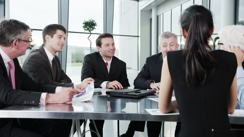 A confident and attractive business team of mixed ages and ethnicity are holding a meeting in a light, modern office building. They are discussing ideas for their business development.  | Shutterstock HD Video #3870668