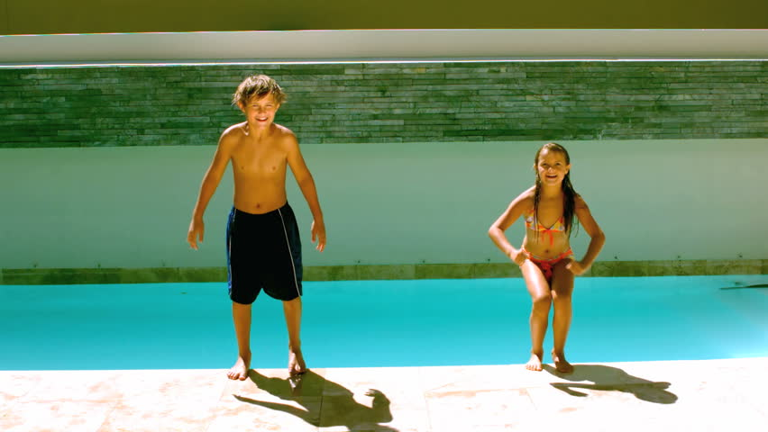 Siblings jumping together in the swimming pool in slow motion at 250 frames per second