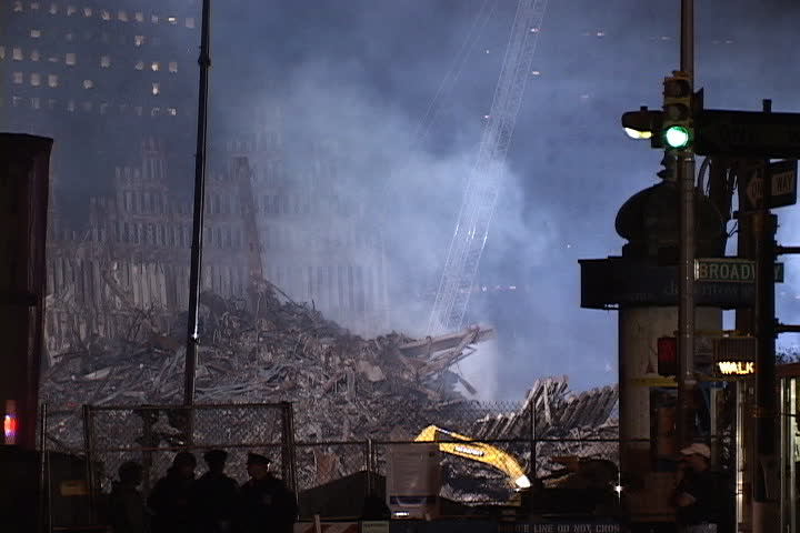 NEW YORK CITY - SEPTEMBER 28, 2001: Smoke rising from floodlit rubble at World Trade Center site. Emergency workers walk past.