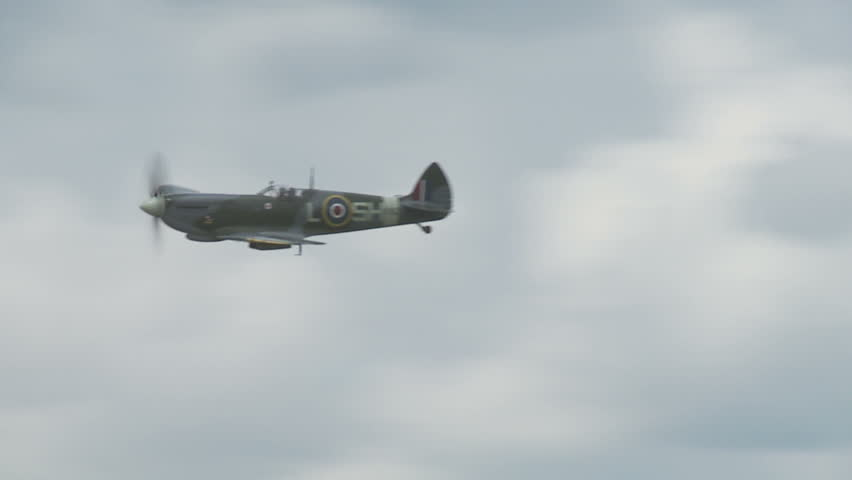 Supermarine Spitfire fighter plane from World War II flying, passing a formation