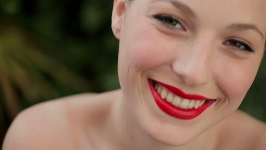 Close up portrait of a young beautiful woman with bare shoulders, wearing bright red glossy lipstick and smiling outdoors, in a green forest background.