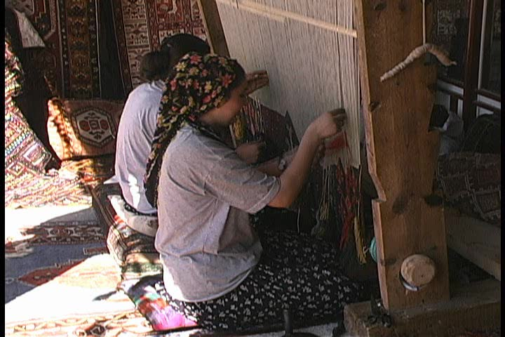 Carpet weavers using a Loom