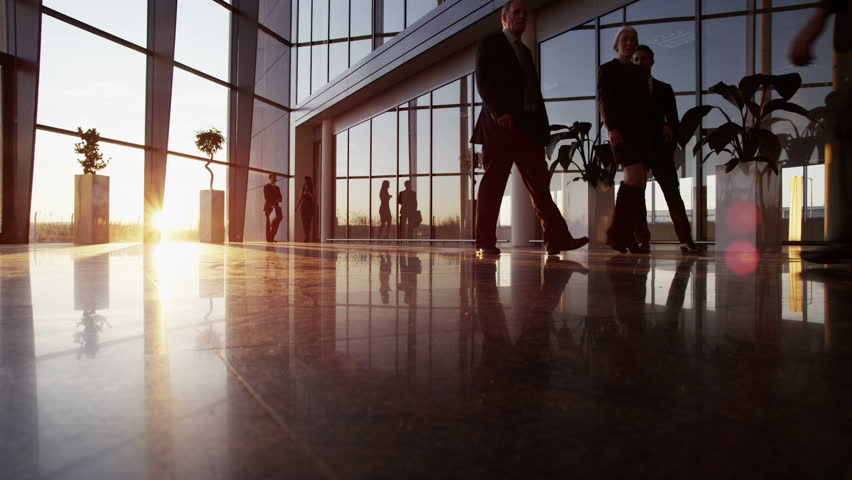 A diverse group of business people are making their way around a busy modern office building as the sun sets outside. | Shutterstock Video #3893504