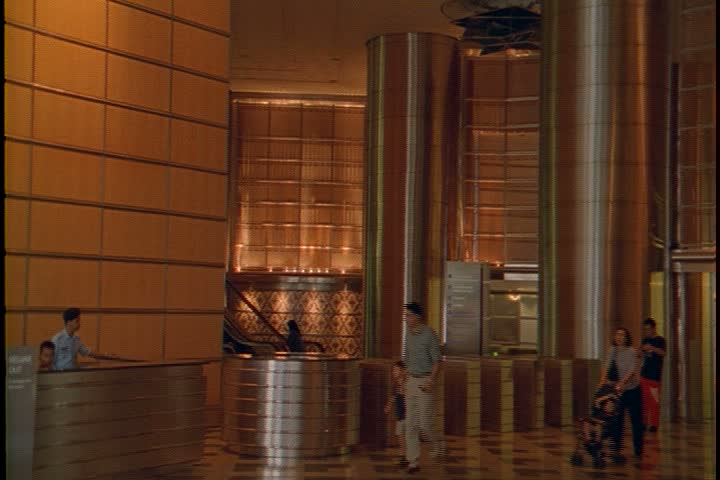 KUALA LUMPUR - OCTOBER 22, 1999: Petronas Towers lobby interiors; CU of brass pillar, camera pans left to show WS of main lobby and information desk, pedestrians walking through lobby.