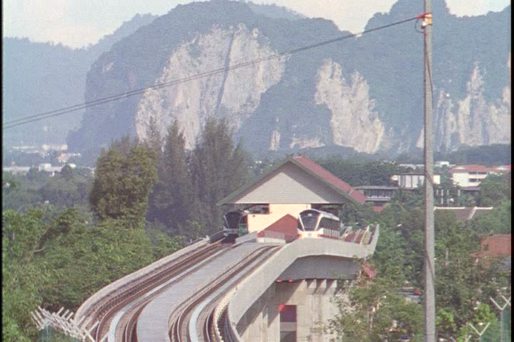 KUALA LUMPUR - CIRCA OCTOBER 1999: Lake Garden tram station with tall green mountains in background. Train leaves the station and heads toward camera.