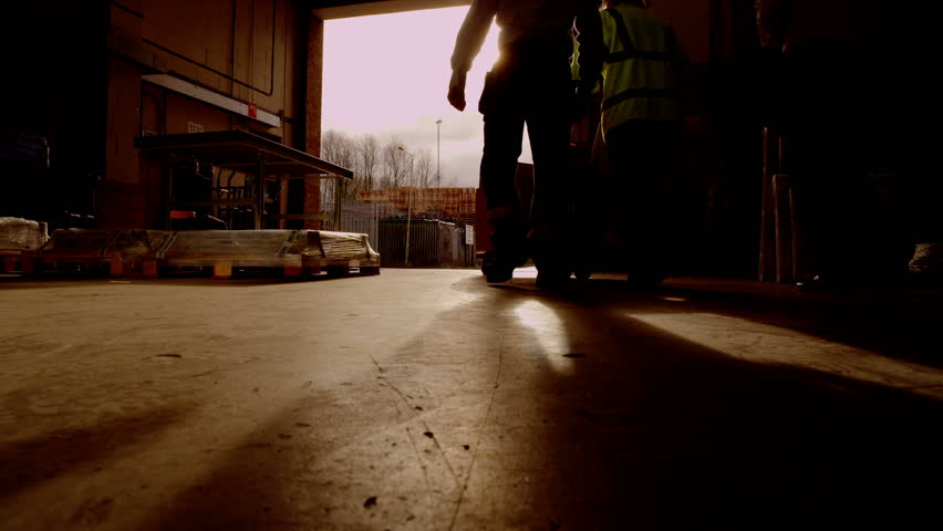 Atmospheric sepia toned clip of workers going about their business in a warehouse or storage facility. Sunlight streams into the space through the open shutter doorway. Low angle.