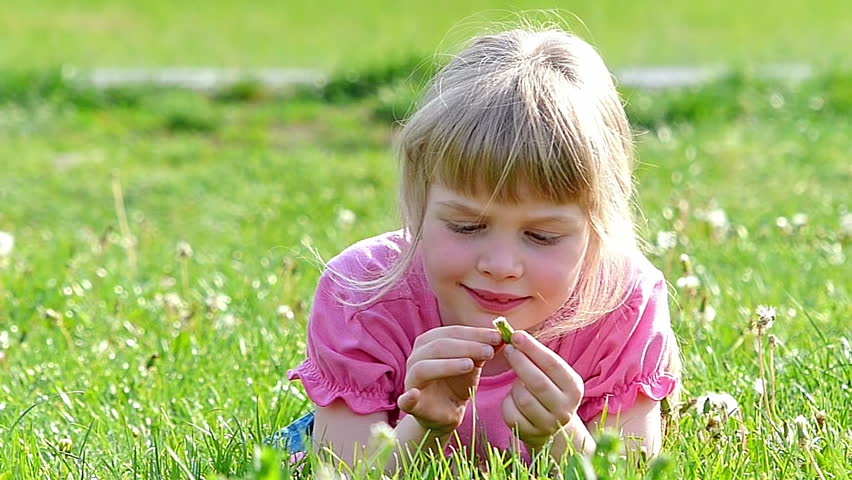 Little girl lying on the grass and playing with a spring's flower,Slow motion,high speed camera