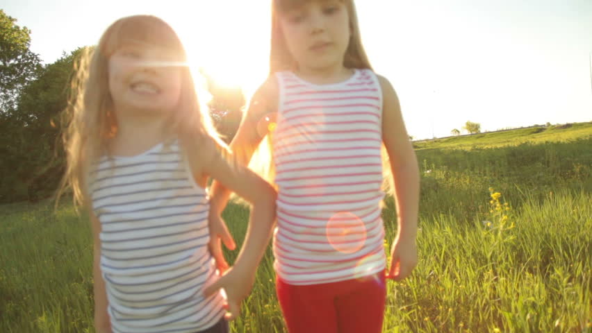Two girls running on grass and smiling with flare